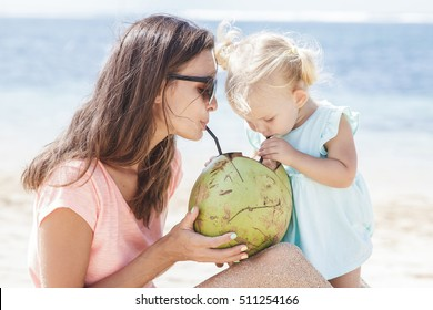 portrait of young mother sharing coconut water with her daughter while enjoying beach vacation