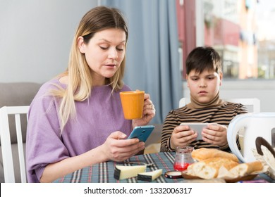 Portrait of young mother and son  using phones during breakfast  indoors
