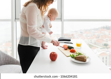 Portrait of young mother standing and holding her little baby while cooking on kitchen with big windows on background