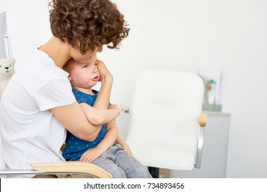 Portrait of young mother trying to calm little boy throwing hysterical tantrum in doctors office, copy space