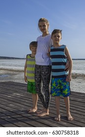 Portrait of young mother and two boys - her sons on the beach dressed in sportswear
