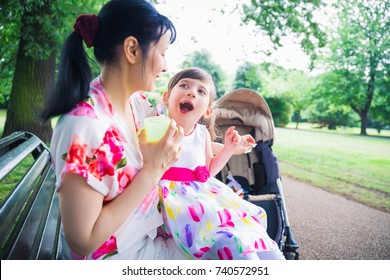 Portrait of young mother who sitting on bench outdoor and keeping on the laps beautiful daughter who is invalid and mother keeping cup of drink in hand
