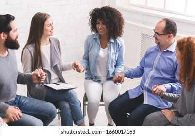 Portrait of young multi-cultural group of people holding hands during therapy session, sitting in trust circle and smiling
