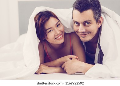 Portrait of young multiethnic couple, Asian woman and Caucasian man, lying together in bed wrapped in blanket, holding hands, looking at camera and smiling. Honeymoon and sexual life concept