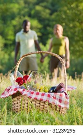 portrait of young multiethnic couple holding hands and picnicking in park