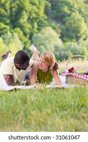 portrait of young multiethnic couple picnicking in park