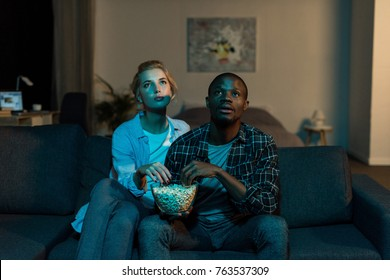 portrait of young multiethnic couple watching film together on sofa at home