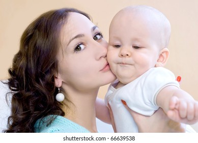 Portrait of young mum together with a small son in a room interior