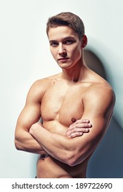Portrait of young muscular man with naked torso standing with hands folded against white wall