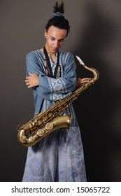 Portrait of young musician standing with saxophone