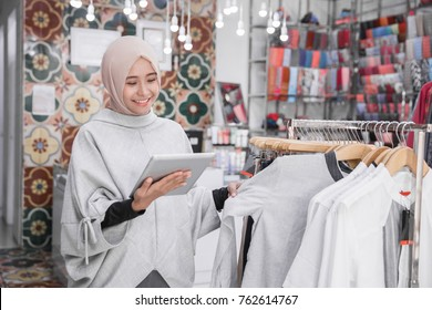 Portrait of a young muslim businesswoman with beautiful smile holding digital tablet checking stock in her fashion boutique, female owner
