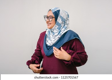 Portrait of a young Muslim Malay woman in a colorful tudung headscarf (hijab) and traditional garb against a white background. She is wearing glasses and is smiling.