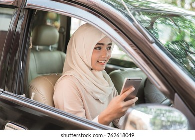 portrait of Young muslim woman driving her car and using mobile phone. dangerous concept