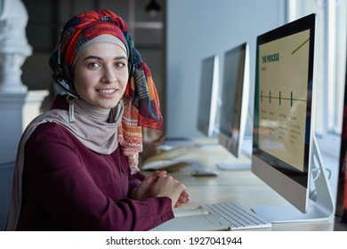 Portrait of young muslim woman in headphones smiling at camera while sitting at the table in front of computer monitor