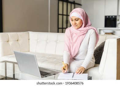 Portrait of a young muslim woman in hijab working at home using laptop computer while sitting on sofa, writing notes, writes a to-do list, working remotely, studying online, freelancer writing details