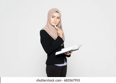 Portrait of a young Muslim woman is holding a book and thinking