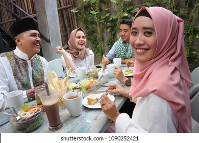 portrait of  young muslim woman looking at camera while other pople eating during ramadan celebration, break fasting at outdoor area enjoying salad ice tea and cake as meal