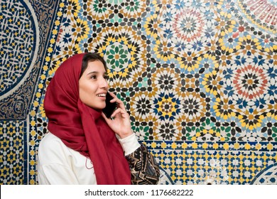 Portrait of young muslim woman with red hijab talking over smart phone in front of traditional arabesque decorated wall