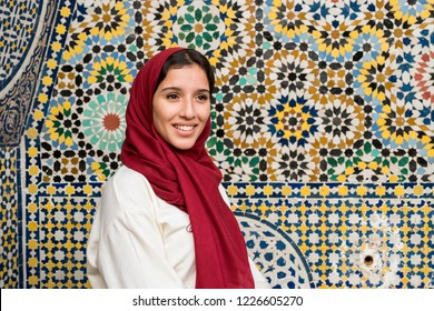 Portrait of young muslim woman smiling in traditional clothing with red hijab in front of traditional arabesque decorated wall