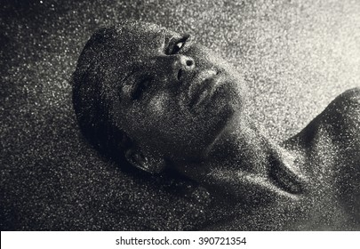Portrait of young  mystical fantasy woman from another world covered with tinsels lying on her back on a floor. Girl from a dream