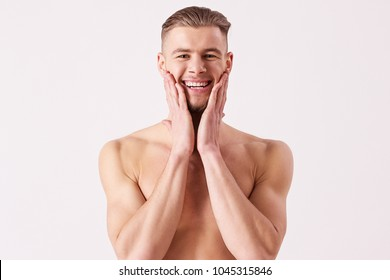 Portrait of young naked man applying aftershave and smiling while standing isolated on white background. Bearded hispter man standing shirtless and touching his face with hands. Men's skin care