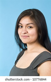 A portrait of a young, naturally beautiful Hispanic woman taken against a blue background.