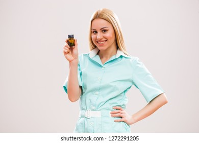 Portrait of young nurse who is holding pills.