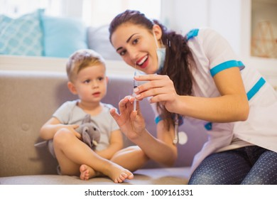 Portrait of the young nurse who sitting on the sofa in the room with the cute little boy and showing the syringe
