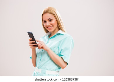 Portrait of young nurse who is using smartphone.