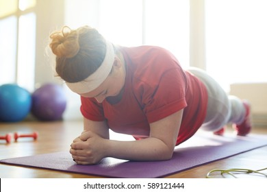 Portrait of young obese woman working out on yoga mat in sunlit fitness studio: holding plank exercise with effort to lose weight