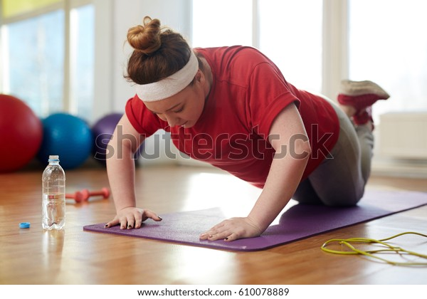 Портрет молодой женщины с ожирением, занятой на коврике йоги в солнечном фитнес-студии: выполнение колено толкать вверх упражнение с усилием похудеть