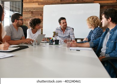 Portrait of young office workers meeting in a boardroom. Team of multi ethnic business people discussing work around conference table.