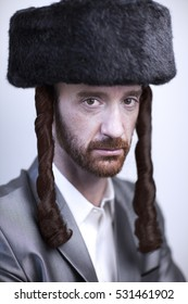 Portrait of a young orthodox Hasdim Jewish man with red beard and black fur hat in a silver business suit