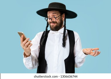 Portrait of a young orthodox jewish man with mobile phone at studio. Purim, business, businessman, festival, holiday, celebration, judaism, religion concept.