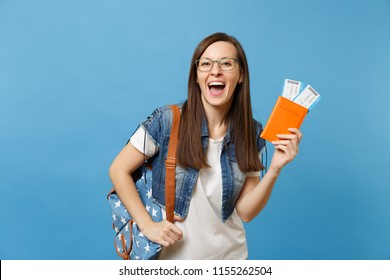 Portrait of young overjoyed woman student in glasses with backpack hold passport, boarding pass tickets isolated on blue background. Education in university college abroad. Air travel flight concept
