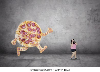 Portrait of young overweight woman is escaping from a pizza while running with fear expression