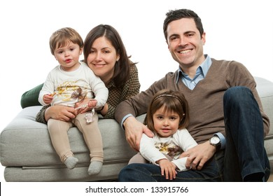 Portrait of young parents with their daughters on couch.Isolated.