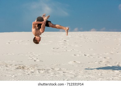 Portrait of young parkour man doing flip or somersault on the sand.