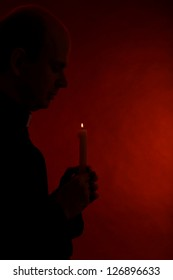 Portrait of young Pastor holding candle in his hand, isolated on black