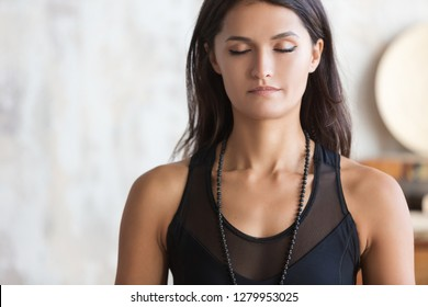 Portrait young peaceful yoga girl wearing black sportswear with closed eyes. Calm girl standing in asana, pose. Ptacticing yoga at home. Close up. Head shot. No stress concept. Breath.