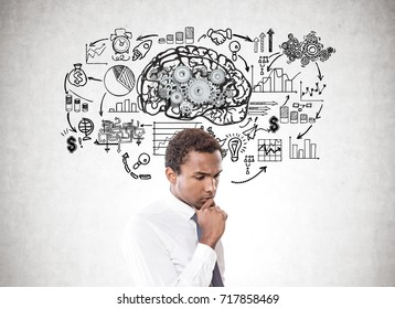 Portrait of a young pensive African American businessman wearing a white shirt and a gray tie. Concrete wall background with a brain with gears and a business plan