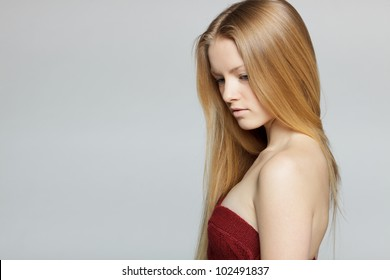 Portrait of young pensive female looking down over gray background