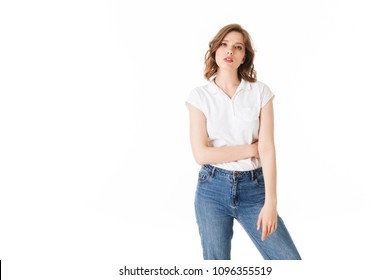 Portrait of young pensive lady standing in t shirt and jeans and thoughtfully looking in camera on white background isolated