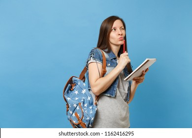 Portrait of young pensive woman student in denim clothes with backpack taking exam thinking about test holding notebook pencil isolated on blue background. Education in high school university college