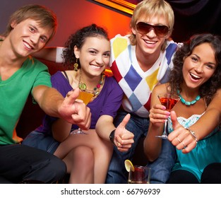 Portrait of young people with flutes showing thumbs up in the nightclub