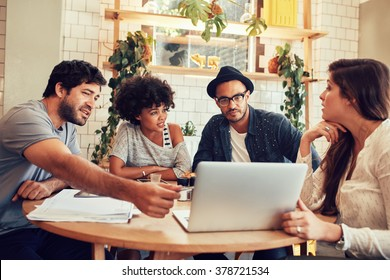 Portrait of young people sitting around a table in cafe with a laptop. Creative team discussing new business project at a coffee shop.