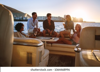 Portrait of young people sitting on a private yacht and drinking. Friends having boat party at sunset.