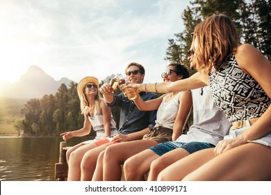 Portrait of young people sitting on a jetty and toasting beers on a sunny day. Happy young men and women hanging out at the lake.