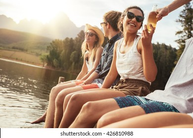 Portrait of young people sitting on a jetty on a sunny day. Happy young men and women enjoying their holiday at the lake.