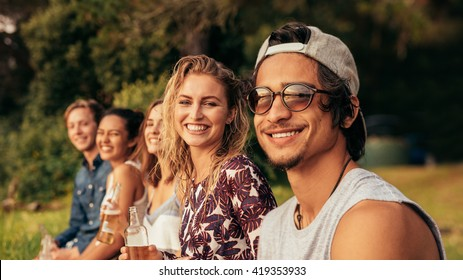 Portrait of young people sitting in a row and looking at camera. Group of friends sitting by a lake and relaxing.